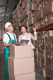 Warehouse worker scanning box with manager holding tablet pc Stock Image
