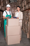 Warehouse worker scanning box with manager holding tablet pc. In a large warehouse Royalty Free Stock Photos