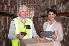 Warehouse worker scanning box with manager. In a large warehouse Stock Photos
