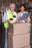 Warehouse worker scanning box with manager. In a large warehouse Royalty Free Stock Photography