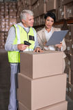 Warehouse worker scanning box with manager. In a large warehouse Royalty Free Stock Photos