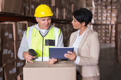 Warehouse worker scanning box with manager Stock Photo