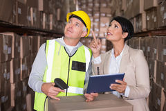 Warehouse worker scanning box with manager. In a large warehouse Royalty Free Stock Photo