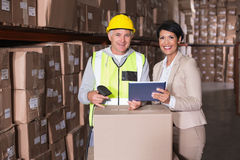 Warehouse worker scanning box with manager. In a large warehouse Stock Photo
