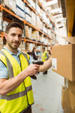 Warehouse worker scanning box while smiling at camera Royalty Free Stock Images