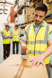 Warehouse worker sealing cardboard boxes for shipping Royalty Free Stock Photos