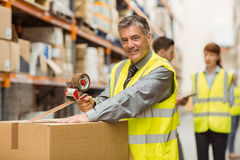 Warehouse worker sealing cardboard boxes for shipping. In a large warehouse royalty free stock image