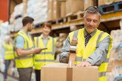 Warehouse worker sealing cardboard boxes for shipping. In a large warehouse royalty free stock images