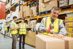 Warehouse worker sealing cardboard boxes for shipping. In a large warehouse royalty free stock photography