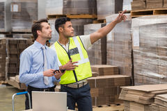 Warehouse worker showing something to his manager. In a large warehouse Royalty Free Stock Photo