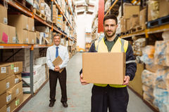 Warehouse worker smiling at camera carrying a box Royalty Free Stock Photos