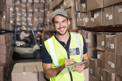 Warehouse worker smiling at camera with clipboard Royalty Free Stock Photo