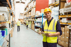 Warehouse worker smiling at camera with clipboard Stock Photo