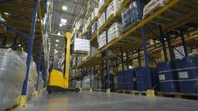 Warehouse worker on stacker loading cargo on shelf stock video