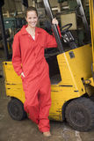 Warehouse worker standing by forklift Stock Images