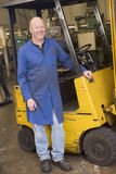 Warehouse worker standing by forklift Royalty Free Stock Image