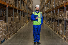 Warehouse worker standing between rows with boxes stock photos