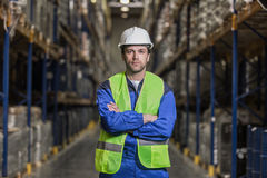 Warehouse worker standing between rows with boxes royalty free stock photography