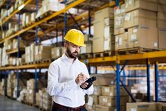 Warehouse worker or supervisor with barcode scanner. A mobile handheld PC with barcode scanner Royalty Free Stock Photo