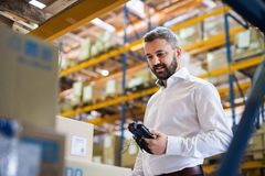 Warehouse worker or supervisor with barcode scanner. A mobile handheld PC with barcode scanner Royalty Free Stock Photography