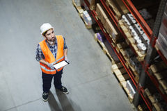Warehouse worker. Supervisor with touchpad looking at goods on shelf Royalty Free Stock Photo