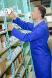 Warehouse worker taking boxed item from shelf. Warehouse stock photography