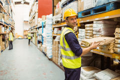 Warehouse worker taking package in the shelf Stock Photos