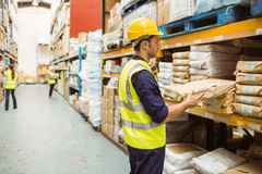Warehouse worker taking package in the shelf Royalty Free Stock Photography