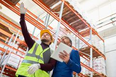 Warehouse Worker Taking to Investor. Low angle portrait of warehouse manager holding clipboard talking to worker wearing hardhat and reflective jacket while Stock Image