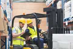 Warehouse worker talking with forklift driver Stock Photography