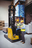 Warehouse worker talking with forklift driver Stock Image