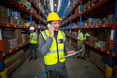 Warehouse worker talking on mobile phone and holding clipboard Stock Photo
