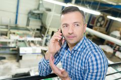 Warehouse worker talking on phone royalty free stock image