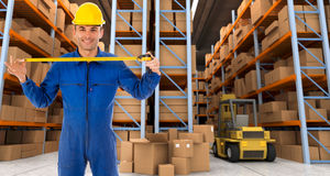 Warehouse worker with tape measure b. Man with helmet and blue overalls in a distribution warehouse extending a tape measure Stock Photography