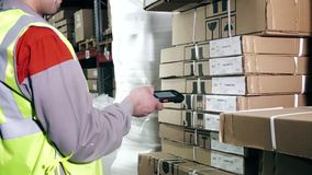 A warehouse worker uses a barcode scanner stock video