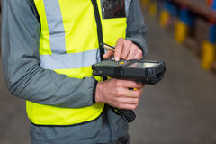 Warehouse worker using barcode scanner machine. Mid section of warehouse worker using barcode scanner machine in warehouse Royalty Free Stock Image