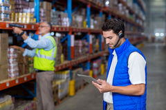 Warehouse worker using digital tablet. In warehouse Royalty Free Stock Image