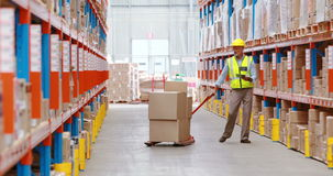 Warehouse worker using digital tablet while checking packages stock footage