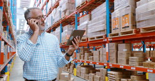 Warehouse worker using digital tablet while talking on mobile phone. In warehouse