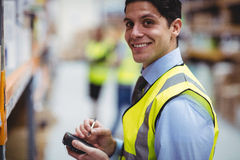 Warehouse worker using hand scanner. In warehouse Stock Image