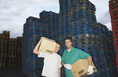 Warehouse Workers Carrying Boxes Against Pallets Stock Photos