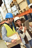 Warehouse workers checking on goods. Store manager with warehouseman checking stock levels Stock Images