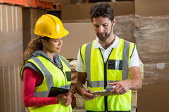 Warehouse workers discussing with clipboard and digital tablet Royalty Free Stock Photo