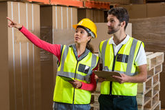 Warehouse workers discussing with clipboard and digital tablet Royalty Free Stock Image