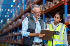 Warehouse workers discussing with clipboard while working stock photos