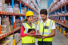 Warehouse workers discussing with clipboard while working Stock Photography