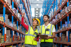 Warehouse workers discussing with clipboard while working Royalty Free Stock Images