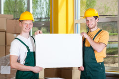 Warehouse workers holding a blank white board Stock Photography