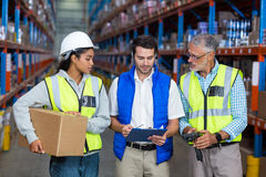 Warehouse workers interacting with each other. In warehouse Royalty Free Stock Photo