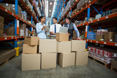 Warehouse workers and manager discussing with laptop. In the warehouse Stock Photo